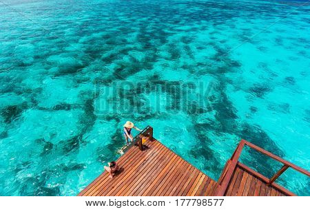 Mother and daughter at wooden dock of overwater villa in Maldives