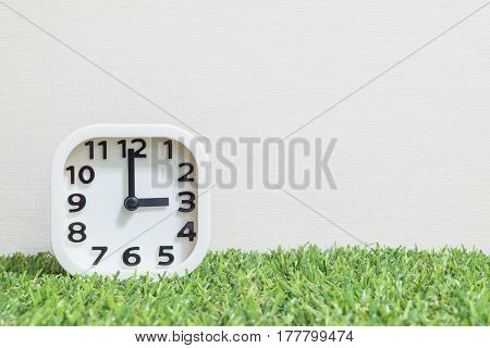 Closeup white clock for decorate in 3 o'clock on green artificial grass floor and cream wallpaper textured background with copy space