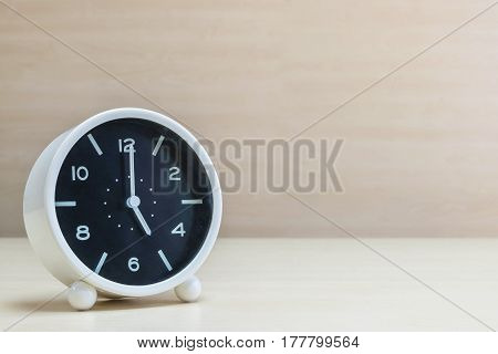 Closeup alarm clock for decorate in 5 o'clock on brown wood desk and wall textured background with copy space