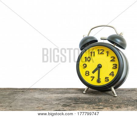 Closeup black and yellow alarm clock for decorate show half past seven or 7:30 a.m. on old brown wood desk isolated on white background with copy space