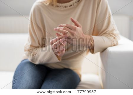 Sad Woman taking off her wedding ring