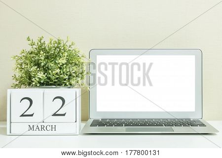 White wooden calendar with black 22 march word with white blank space at center of computer notebook on white wood desk and cream wallpaper textured background selective focus at the calendar