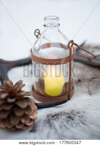 Rustic lantern with yellow candle burning