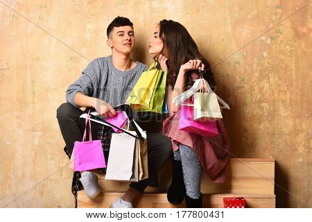 smiling happy couple of pretty sexy girl or cute fashionable woman with long brunette curly hair and young guy or handsome man holds hangers colorful shopping bags or packages on beige background