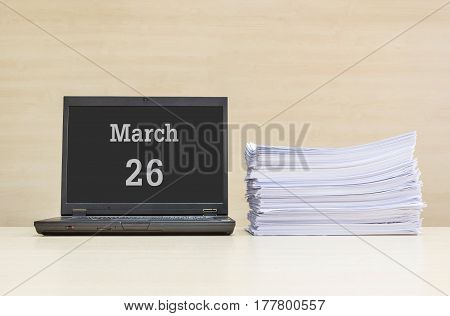 Closeup computer laptop with march 26 word on the center of screen in calendar concept and pile of work paper on wood desk and wood wall in work room textured background with copy space