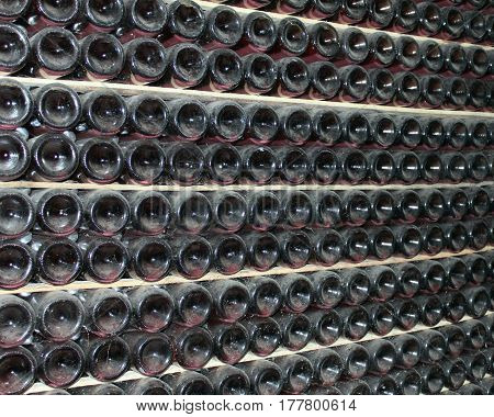 large stack of wine bottles in winery cellar