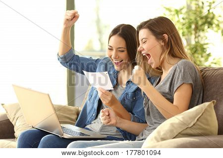 Excited roommates reading a bank notification sitting on a sofa in the living room at home