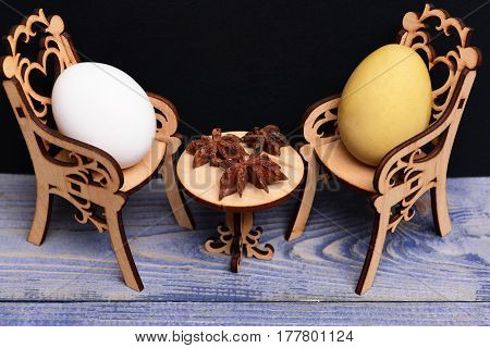 Easter Egg In Wooden Chairs At Table With Badian Spice