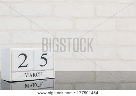 Closeup white wooden calendar with black 25 march word on black glass table and white brick wall textured background with copy space selective focus at the calendar