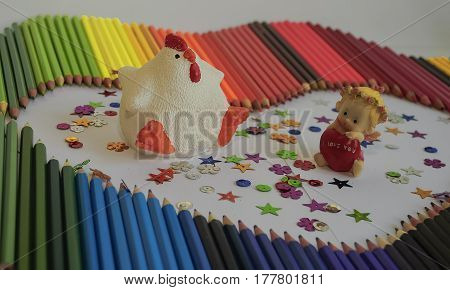 Among the multi-colored pencils figurines white chicken with red comb and a little angel with a red heart in his hands with the words