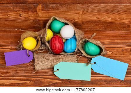 easter colorful eggs painted in bright colors in burlap sack on brown wood on wooden background with shopping tag spring holiday celebration copy space