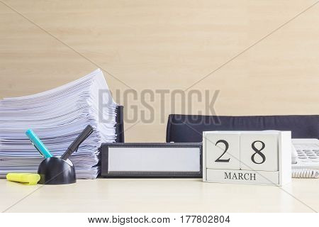 Closeup white wooden calendar with black 28 march word on blurred brown wood desk and wood wall textured background in office room view with copy space selective focus at the calendar
