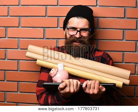 Bearded man long beard. Brutal caucasian smiling happy unshaven hipster holding craft paper rolls piggy bank on laptop in checkered shirt with hat and glasses on brown brick wall studio background