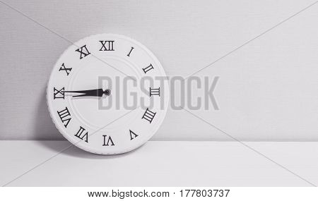 Closeup white clock for decorate show a quarter to nine or 8:45 a.m. on white wood desk and wallpaper textured background in black and white tone with copy space