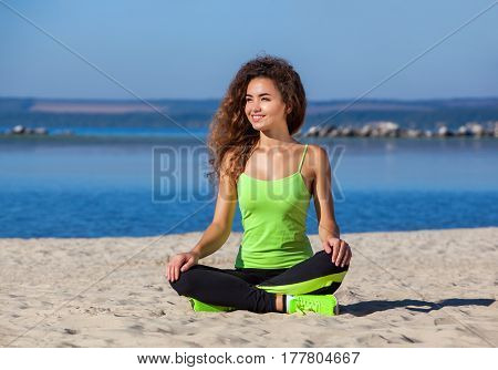 Young slim girl with curly hair in black and light green tracksuit sitting after a workout in the sand on the seashore. The concept of a healthy lifestyle and body care.