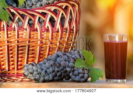 Bunch of grapes and a glass of grape juice a wicker basket with grapes in the sun