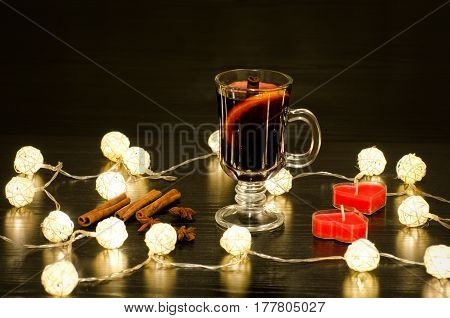 Mug of mulled wine with spices candles in the shape of a heart cinnamon sticks star anise. Illumination of rattan lanterns on a black wooden table