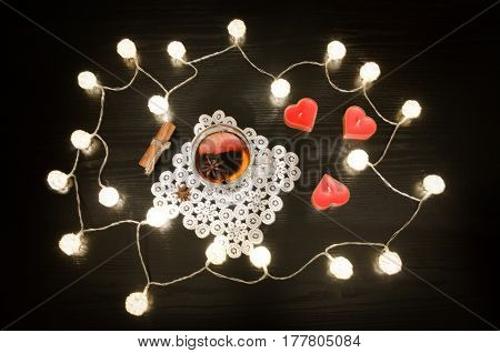 Candles in the shape of a heart mulled wine with spices on a lacy napkin cinnamon. Rattan lanterns on black wooden table top view