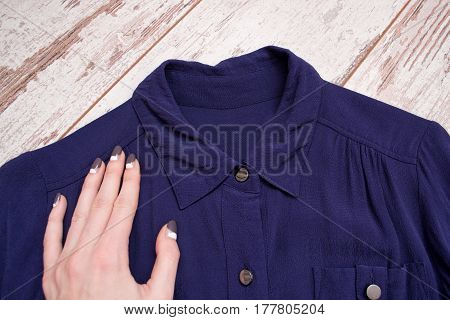 Woman's hand on the collar of a blue shirt. Wooden background. Fashionable concept. View from above
