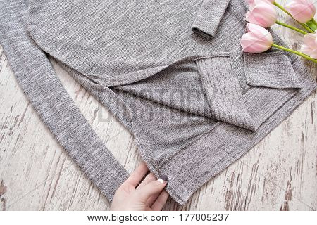 Inner part of a gray sweater a female hand tulips. Fashion element top view