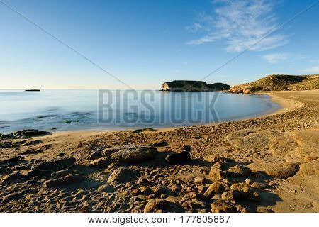 Beach of the Higuerica in the natural place of the Four Coves. Long exposure photography at sunrise on the coast of Aguilas, Murcia.
