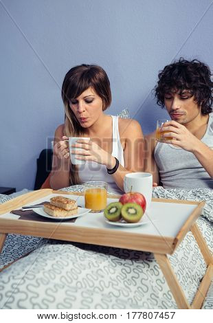 Young happy couple in love having breakfast in bed served over a tray at home. Couple home lifestyle concept.