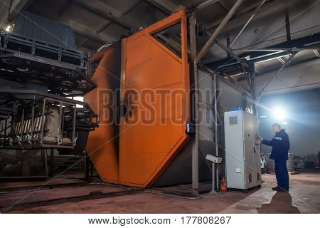 Molding Plastics In The Huge Factory Oven. Worker Is Controlling The Molding Process From Control Pa