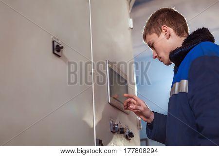 Professional Industrial Engineer Adjusting Modern Machine Settings.