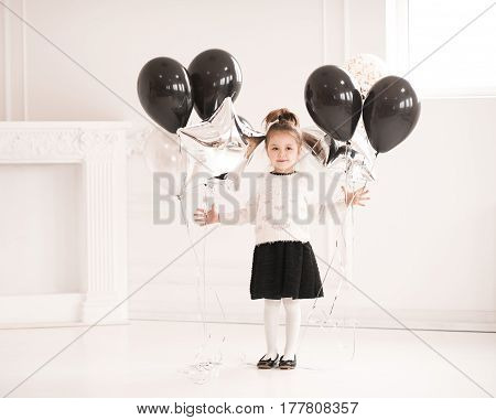 Cute kid girl 5-6 year old holding balloons in room. Looking at camera. Childhood.