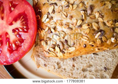 Composition Of Whole Grain Bread Buns And Red Fresh Cut In Half Tomato On A Plate On Wooden Table Ba