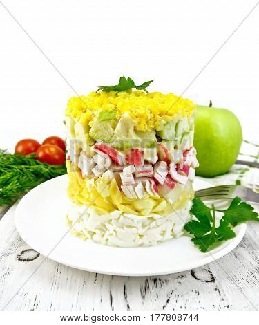 Salad of crab meat, cheese, eggs and green apple in the plate, napkin, background dill on a wooden board