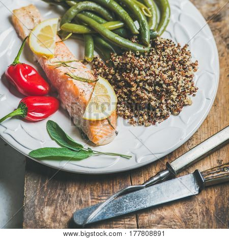 Healthy protein rich dinner plate. Oven roasted salmon fillet with multicolored quinoa, chilli pepper and poached green beans on rustic wooden board, square crop. Clean eating, dieting food concept