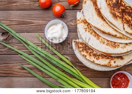 Quesadilla with chicken , green onions, with dressing on wooden table