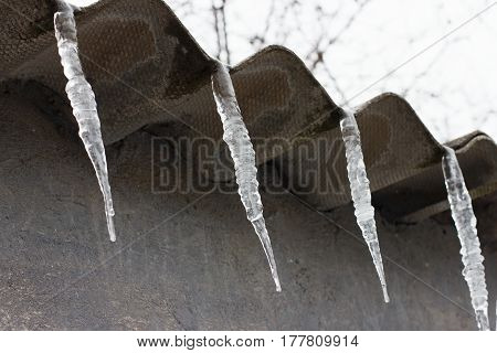 Icicles Hanging From The Roof On A Background Of  Wall