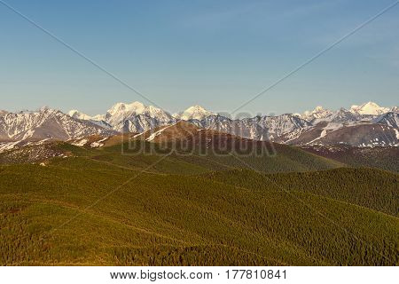 Scenic top view on the snowy mountain peaks and mountain slopes covered with forests on the background of blue sky and clouds