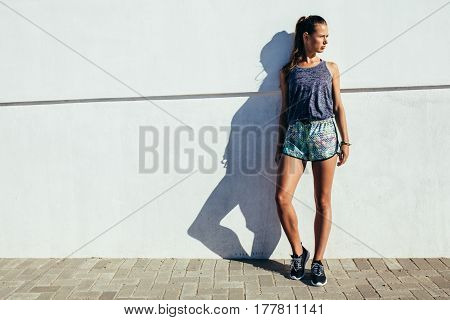 Full length shot of healthy young female leaning to a wall outdoors and looking away. Fitness woman relaxing after running workout.