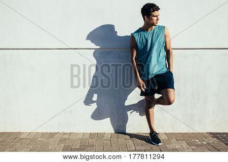 Full length shot of healthy young male runner leaning to a wall outdoors and looking away. Fitness man relaxing after running workout.