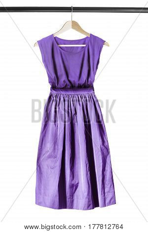 Retro styled purple dress on wooden clothes rack isolated over white