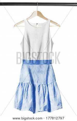 White and blue combined sundress on wooden clothes rack isolated over white
