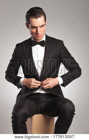 seated young man in tuxedo buttoning his coat and looks to side on grey background