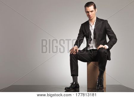 man in open tuxedo and undone bowtie sitting on wooden box in studio