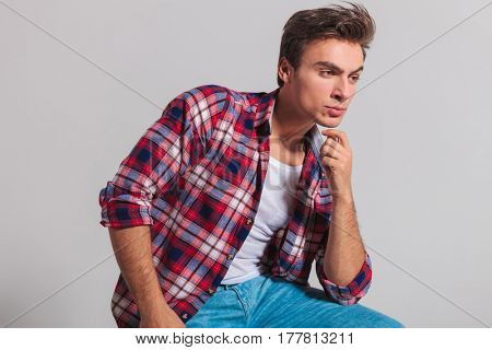 side view of a seated pensive young casual man on grey studio background