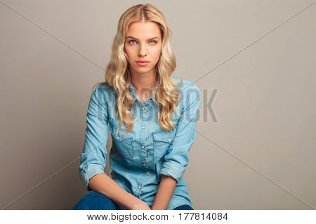 young seated blonde casual woman looking at the camera on light grey background