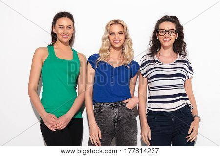 three young casual women laughing together on white background