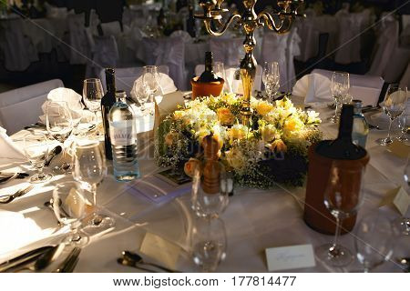 Candleholder stands in the garland of white and yellow roses on a dinner table