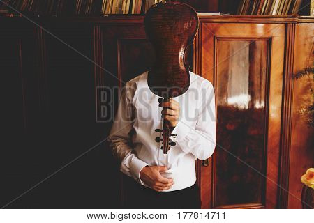 Man Holds A Violin In The Front Of His Face