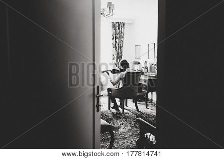 A View From Behind The Door On A Man Playing A Violin
