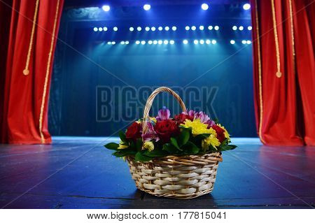 wicker basket with flowers standing on the stage.on the background of red theater curtain