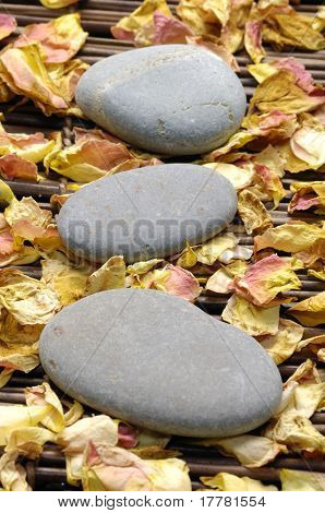 Stack of stone with rose withered petals on bamboo mat