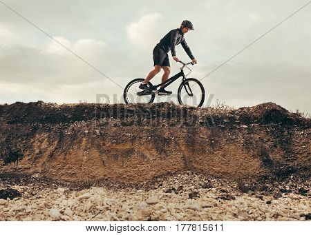 Side view of a person riding a trial bicycle on the hill. Horizontal outdoors shot.